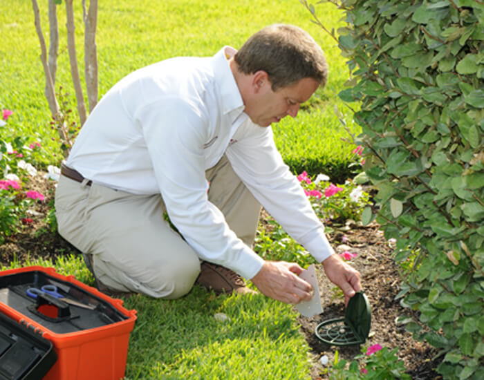 a lawn care specialist is fixing a sprinkler