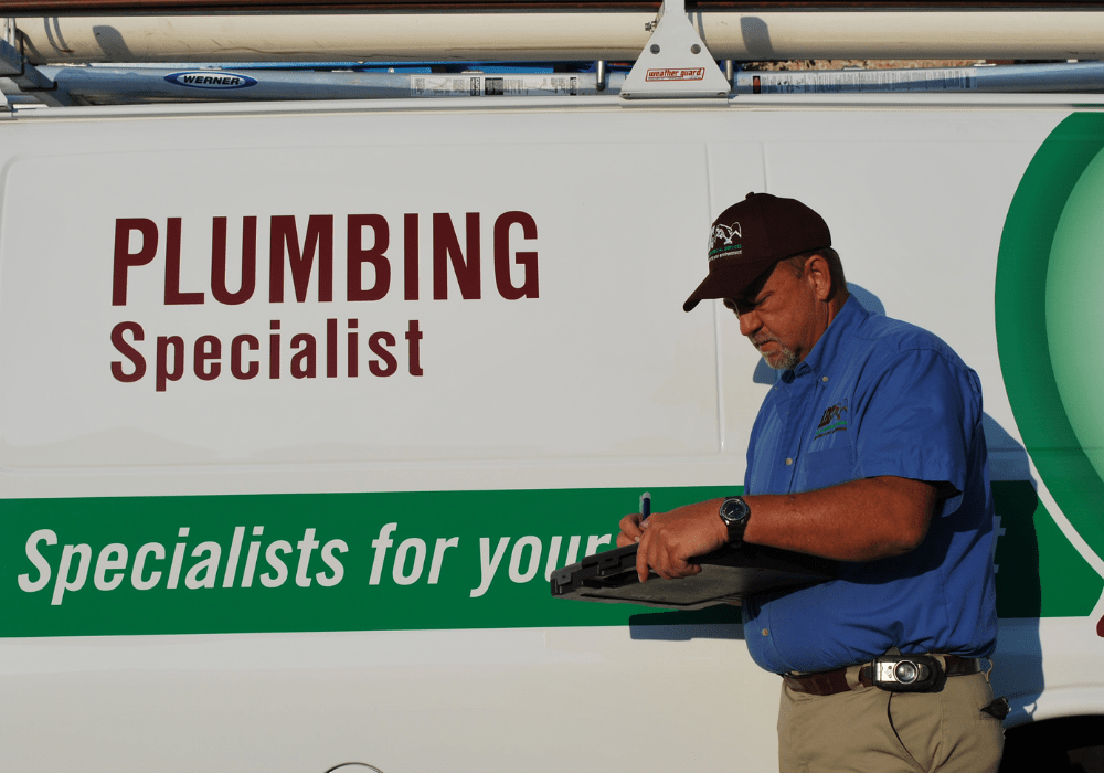 a commercial plumber writing a report of the plumbing services provided for a business