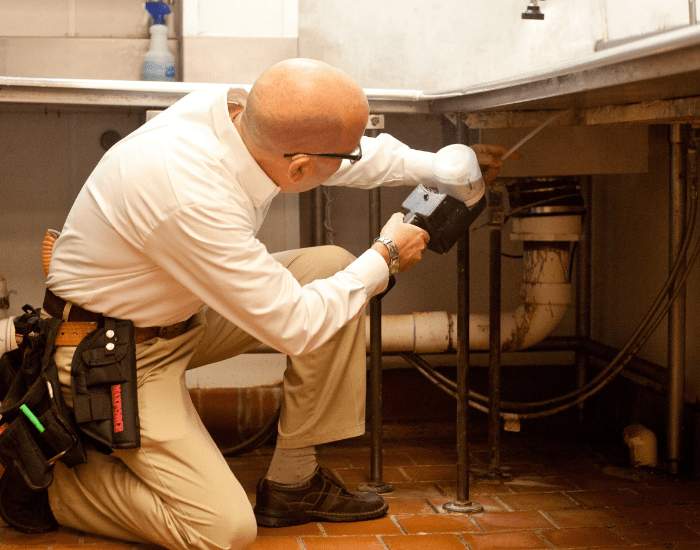 an ABC commercial pest control technician performing an inspection at a restaurant