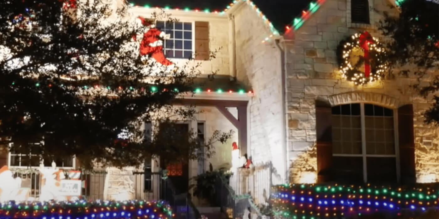 ABC professionals hanging Christmas decorations on a home
