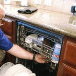 un especialista reparando un lavavajillas descompuesto