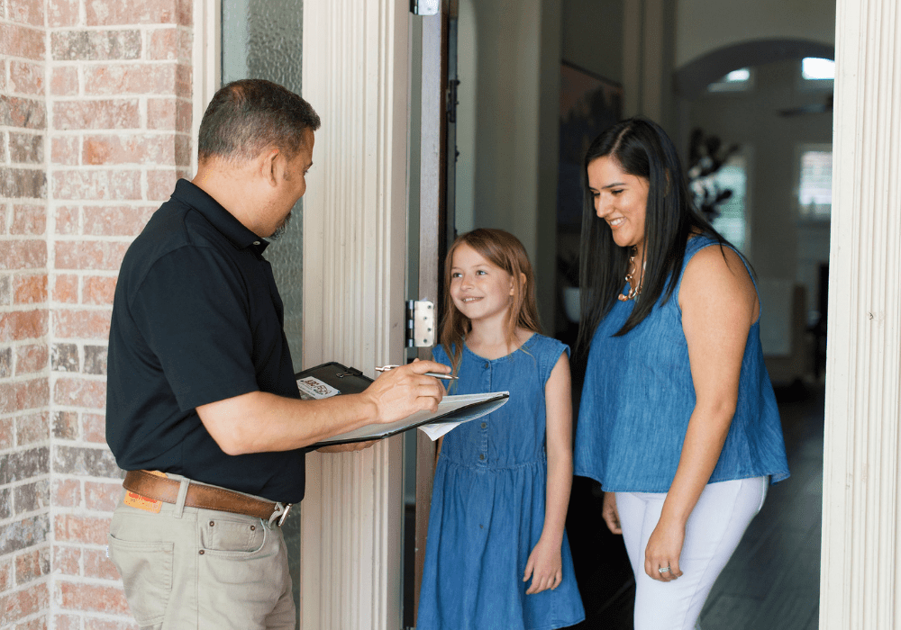 an ABC specialist at the door of a customer and her daughter talking about ABC services