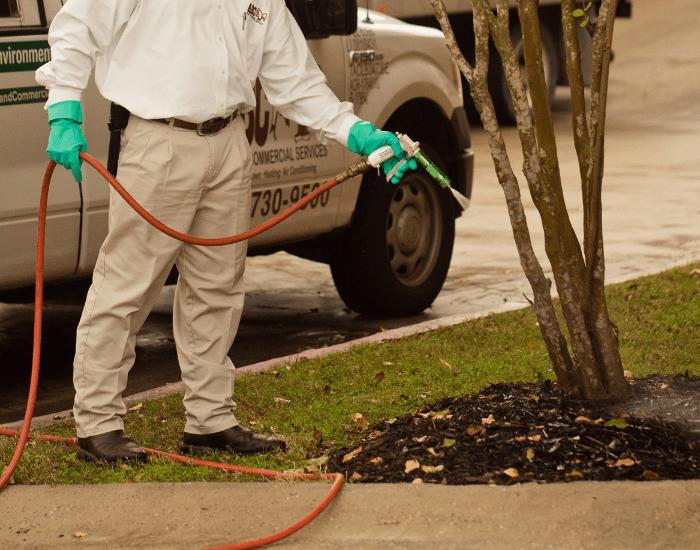 an ABC lawn care specialist fertilizing a commercial lawn