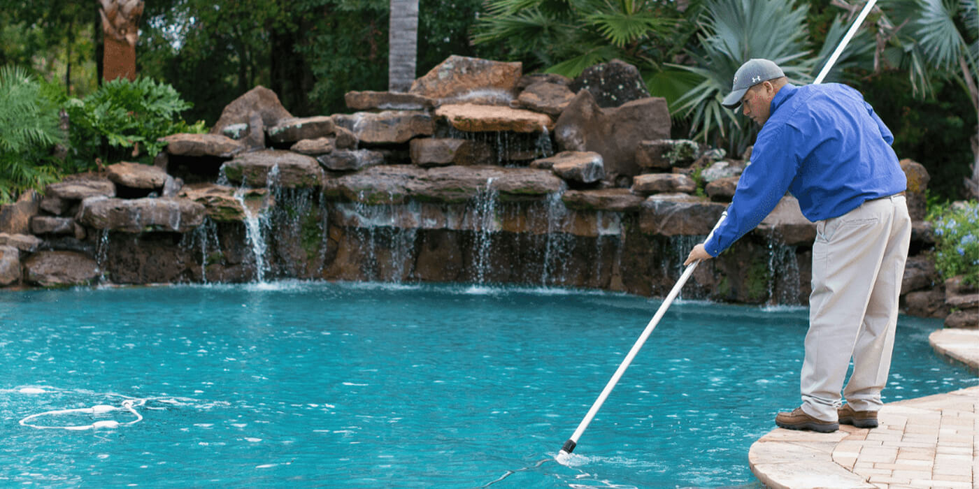a certified pool professional cleaning a homeowner's pool
