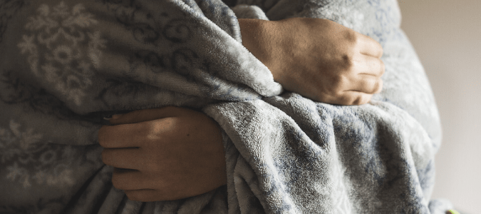 Person wrapped in blanket when em heat is not working
