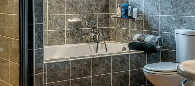 a toilet and a gray bathtub