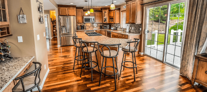 A kitchen with hardwood floors and wooden cabinets