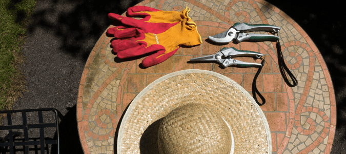 a hat, gardening shears and gloves to get started with spring landscaping cleanup