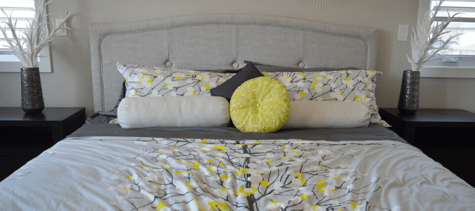 A bed with a gray comforter and yellow and white pillows