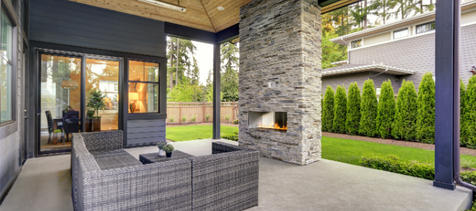 A backyard with a fireplace and a gray couch