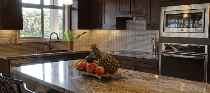 A brown kitchen with a granite countertop