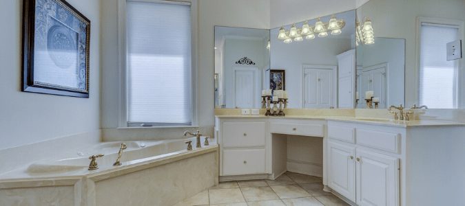 A cream colored bathroom that is suffering from signs of hard water