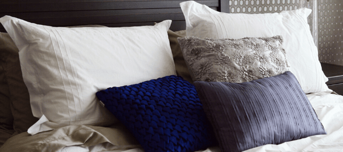 Decorative pillows on a gray bed
