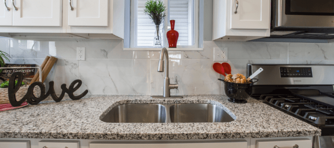 A stainless steel sink with a garbage disposal unit installed in a granite countertop
