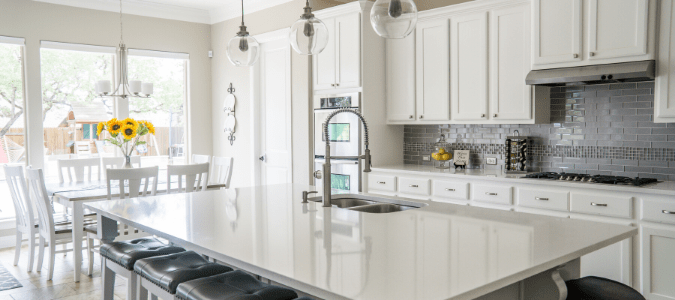 A gray kitchen with white cabinets