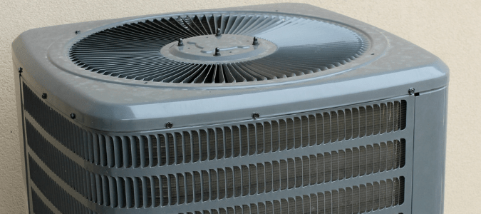 A gray outdoor air conditioning unit with dirty condenser coils