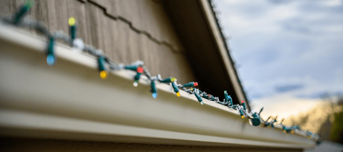 Christmas lights attached to gutters with plastic clips