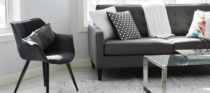 A light grey living room with a dark grey couch and freshly painted white trim
