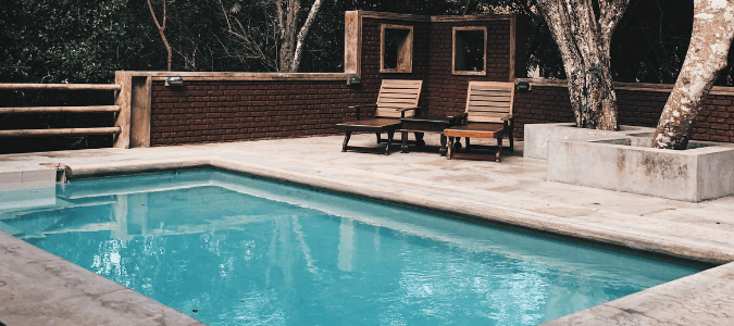a pool at a home with two deck chairs and a retaining wall