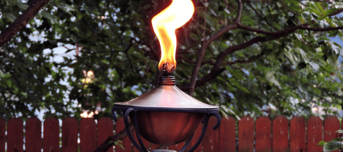 a lit tiki torch in hopes the smoke will keep mosquitoes away