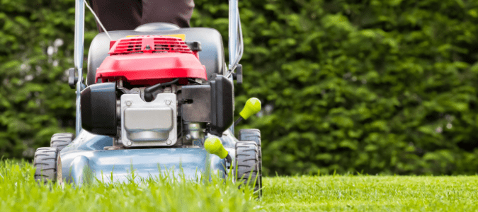 a homeowner mowing the lawn as a part of their fall lawn maintenance routine