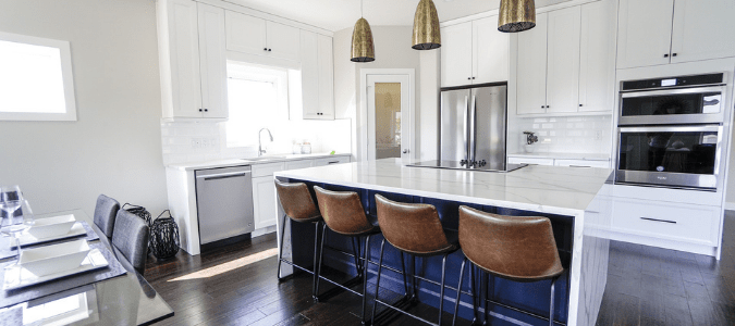 a stainless steel fridge in a white kitchen with brown barstools