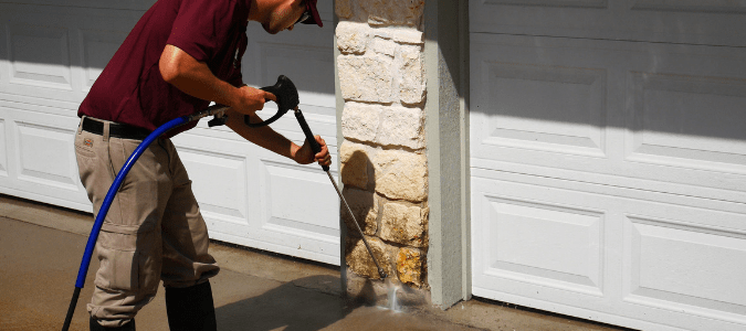 a homeowner pressure washing the stone exterior of their home