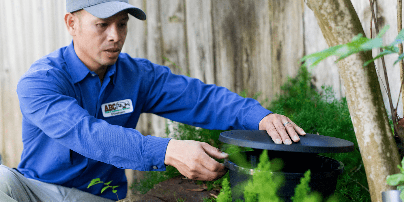 a pest control specialist setting up mosquito misting stations in a yard