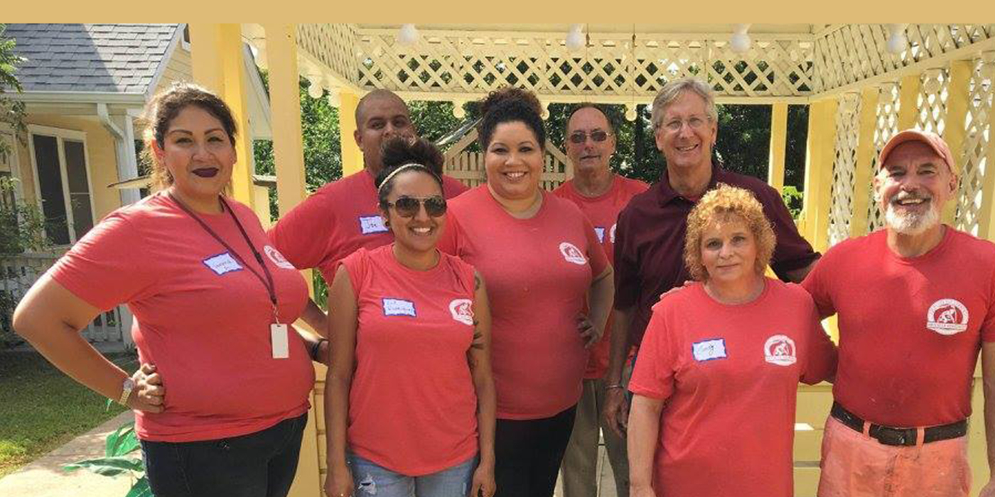 A group of smiling ABC employees at a Habitat for Humanity event