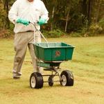 un especialista en jardinería fertilizando el césped de una casa