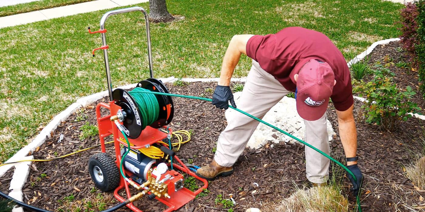 an ABC plumbing specialist feeding a hose down a drain