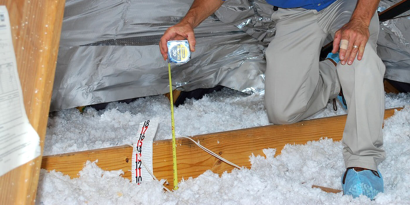 an insulation specialist measuring insulation in a home