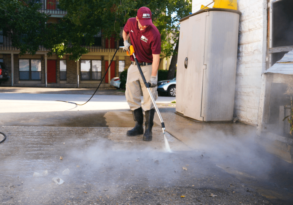 a ABC specialist power washing the driveway of a commercial building