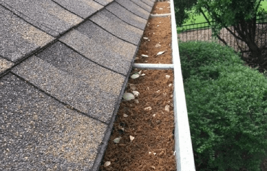 a gutter running along side a roof before ABC specialist have cleaned it; it is filled with dirt and debris.
