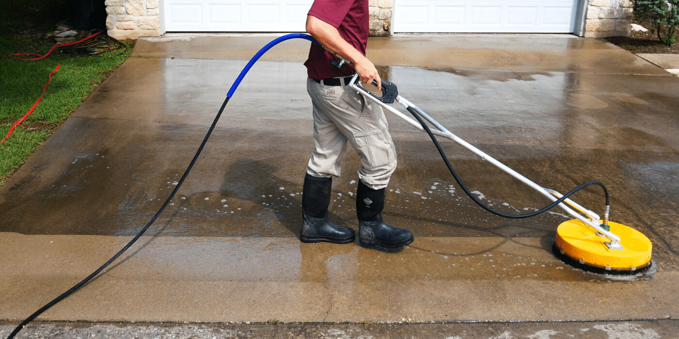 a specialist power washing a homeowner's driveway