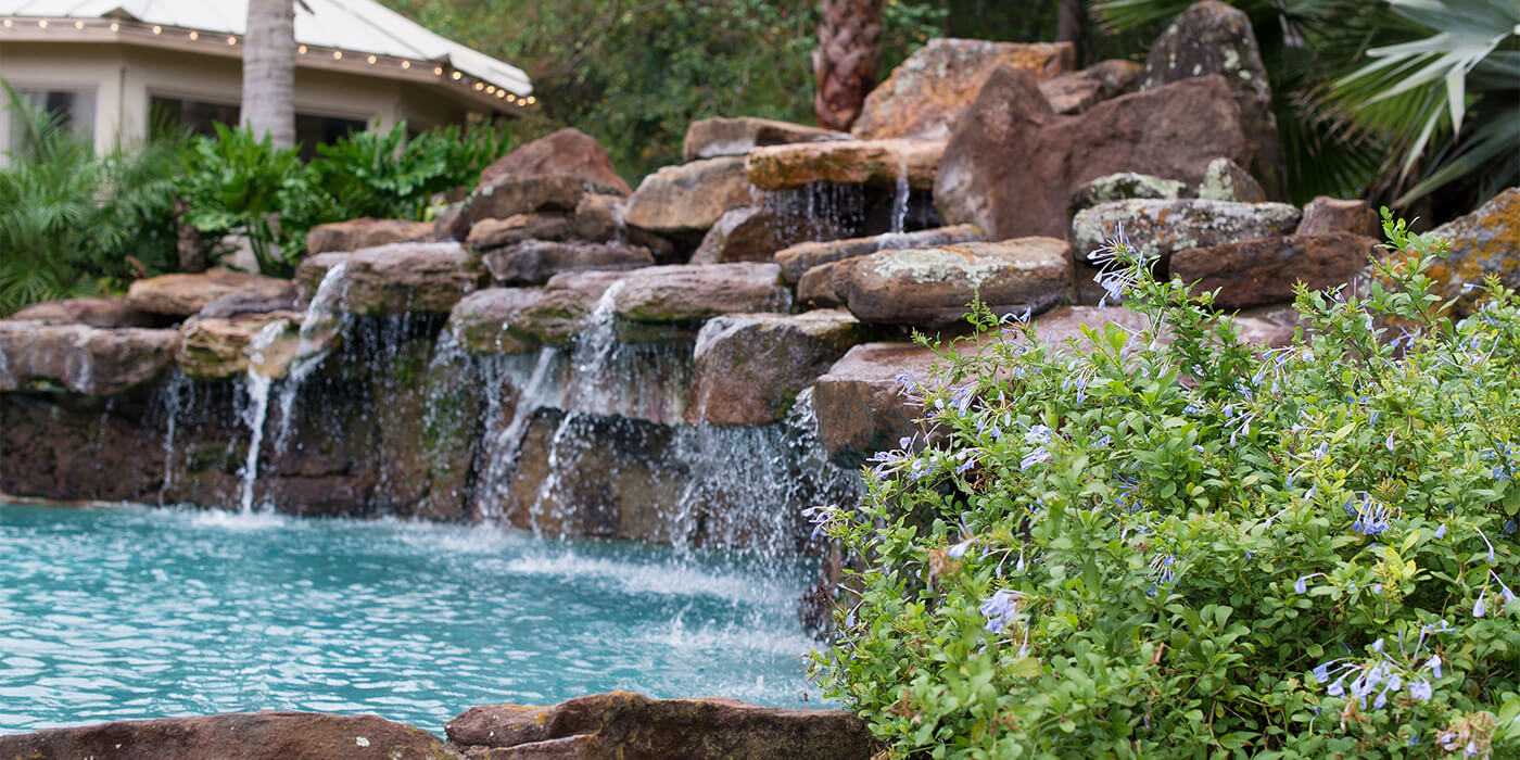 an outdoor pool , done by ABC experts, with a waterfall cascading down a rock wall into the water