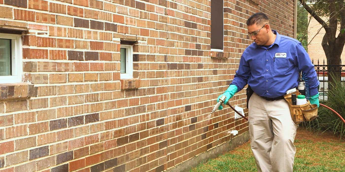 Un técnico de ABC en uniforme habla sobre una reciente llamada de servicio con una clienta y su hija en la puerta