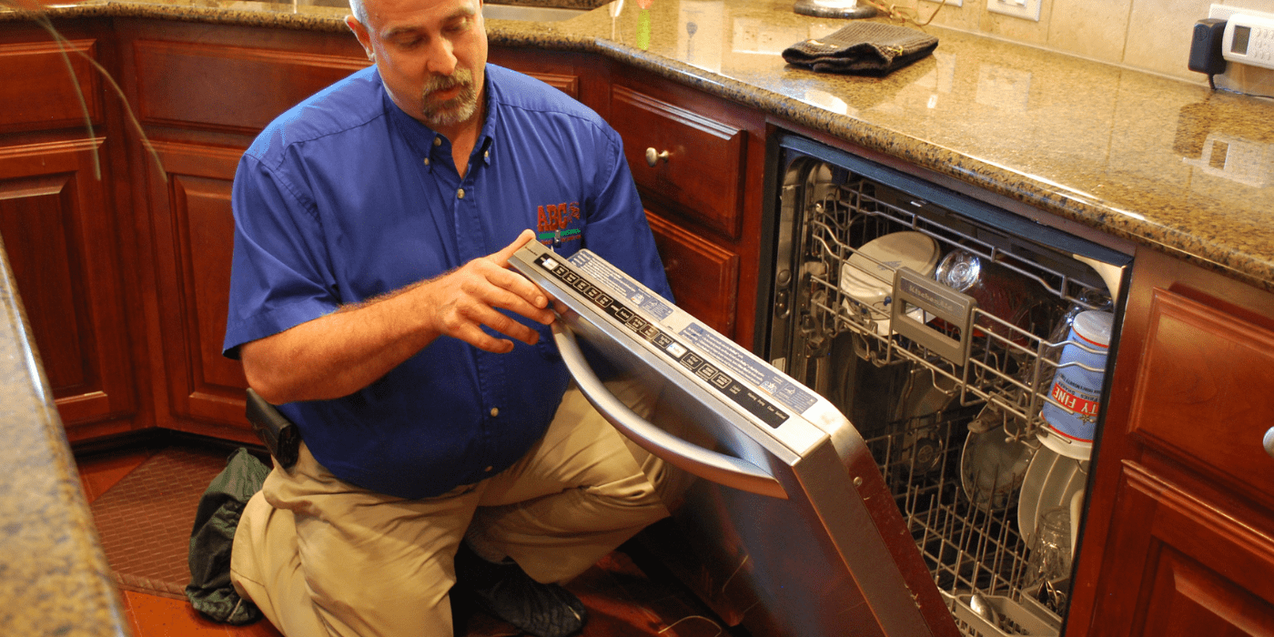 an appliance repair specialist making repairs to a dishwasher