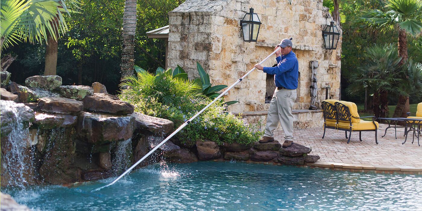 an ABC specialist cleaning a pool