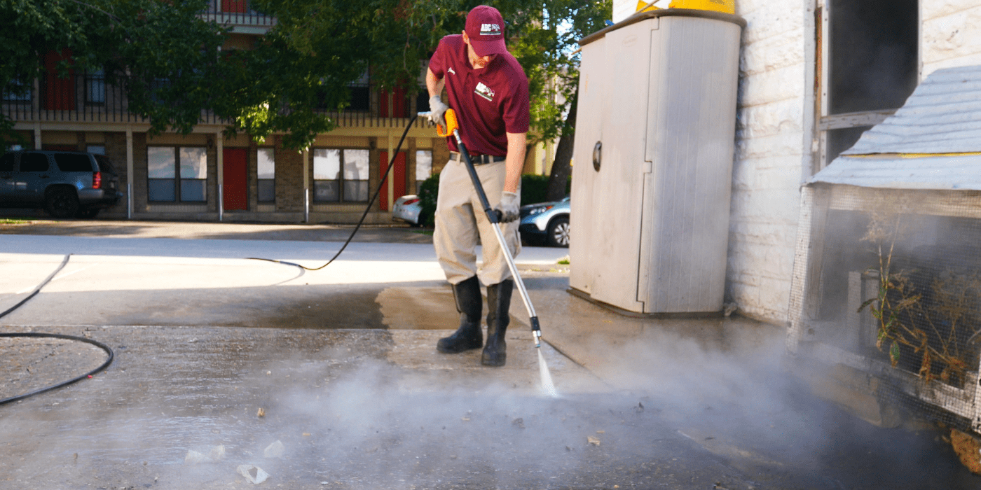 a commercial services specialist power washing a sidewalk outside of a business